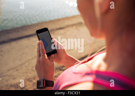 Close up shot of woman reading a text message on her mobile phone. Sports woman using smart phone while taking a - Stock Photo