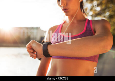 Young fitness woman looking at her smart watch while taking a break from outdoor workout. Sportwoman checking pulse - Stock Photo