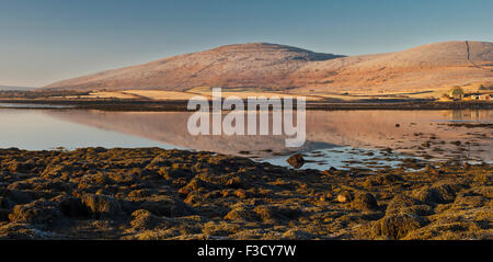 A still morning around dawn at Finavarra, the Burren, County Clare, Ireland, with the limestone mountains reflected - Stock Photo