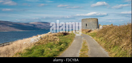 Track leading to the Martello tower at Finavarra Point, County Clare, with the Burren Mountains in the background - Stock Photo