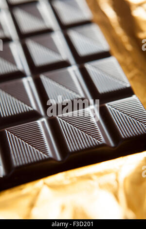 Close Up Of Plain Chocolate Bar On Foil Wrapper - Stock Photo