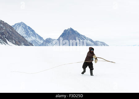 Inuit young boy practicing with traditional dog whip on the floe edge, Baffin bay, Nunavut, Canada. - Stock Photo
