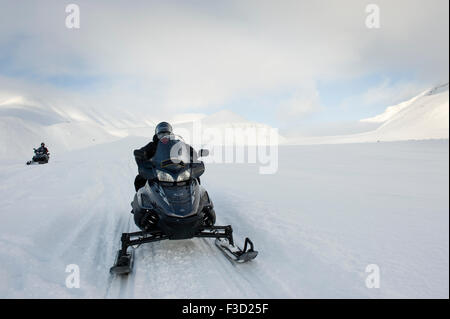 Man on snowmobile on it's way in a snowcovered landscape with glacier behind, Semmeldalen, Spitsbergen, Svalbard, - Stock Photo