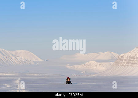 Man on snowmobile on it's way in a snowcovered landscape with Tunabreen glacier behind, Tempelfjorden, Spitsbergen, - Stock Photo