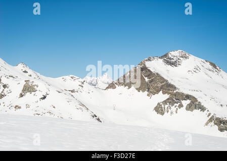 Stunning view of high mountain peaks in the italian alpine arc, in a bright sunny day of winter. Candid snowy slope - Stock Photo