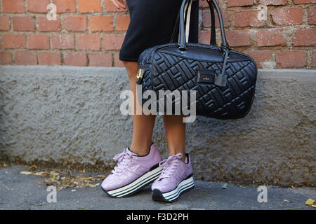 Woman poses for photographers with Hogan bag and shoes before Fendi show during Milan Fashion Week Day 2 - Stock Photo