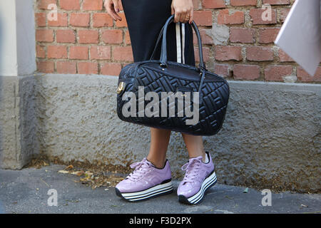Woman poses for photographers before Fendi show with Hogan bag and shoes during Milan Fashion Week Day 2 - Stock Photo