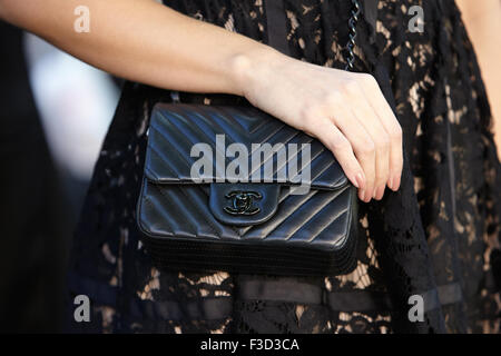 Woman poses for photographers before Fendi show with Chanel bag during Milan Fashion Week Day 2 - Stock Photo