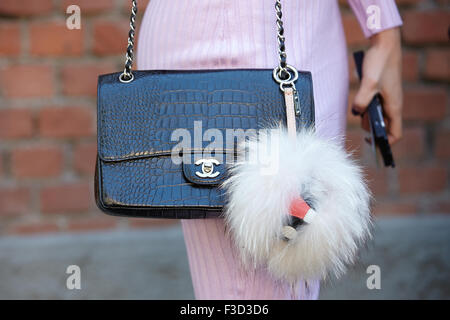 Woman poses for photographers before Fendi show with Chanel crocodile bag during Milan Fashion Week Day 2 - Stock Photo
