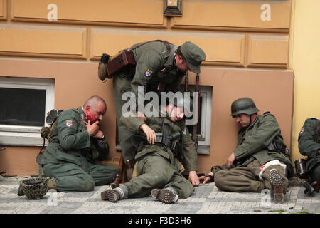 Reenactors uniformed as soldiers of the Russian Liberation Army (ROA) pretend to be injured during the reenactment - Stock Photo