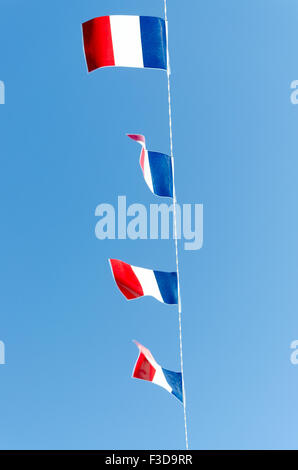 Four French flags on a blue sky background - Stock Photo
