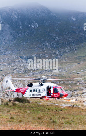 As dusk falls, the Coastguard Rescue Helicopter lands ready to assist a walker injured descending Tryfan - Stock Photo