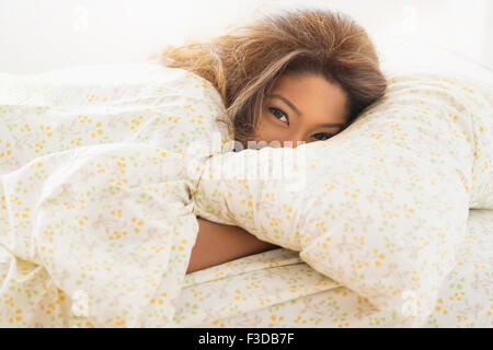 Young woman lying in bed - Stock Photo