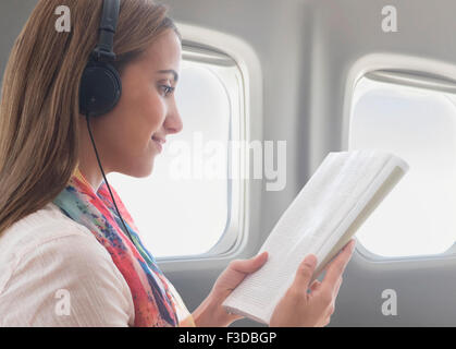 Young woman wearing headphones while reading book on plane - Stock Photo