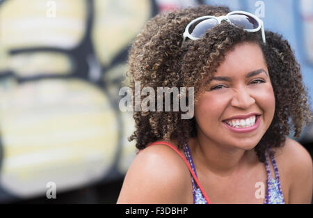 Portrait of smiling young woman with curly hair - Stock Photo