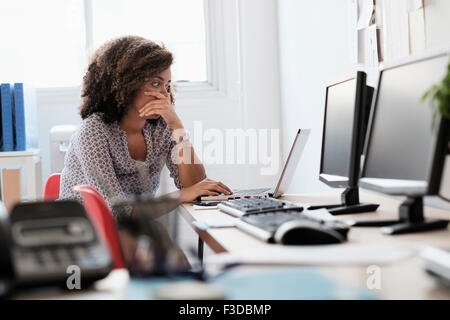 Young woman working at office - Stock Photo