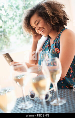 Young woman using smart phone at restaurant - Stock Photo