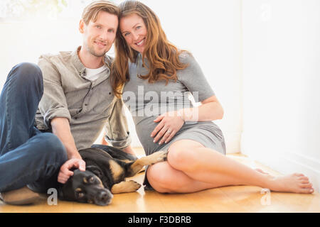 Portrait of mid-adult couple with dog indoors - Stock Photo