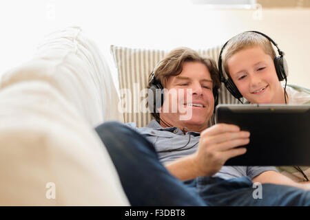 Man using tablet pc with his son (8-9) on sofa - Stock Photo