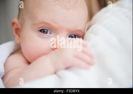 Portrait of baby girl (2-5 months) in mother's arms - Stock Photo