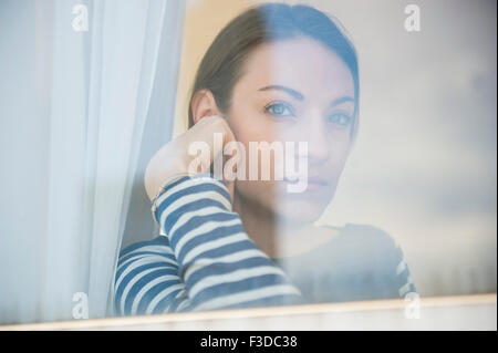 woman looking through window - Stock Photo