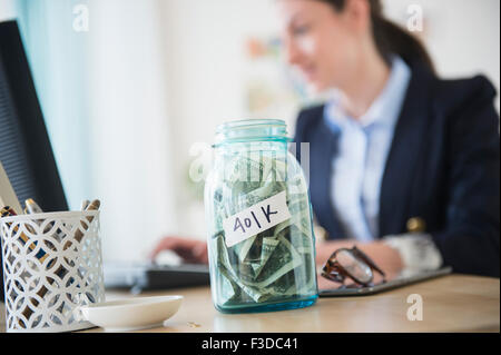 Woman in office with jar full of money on her desk