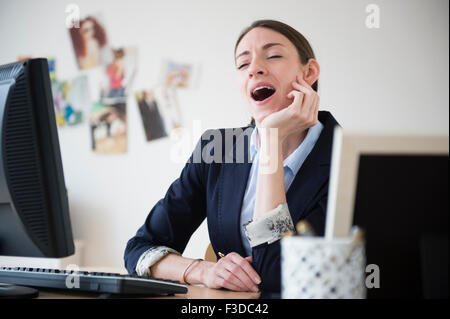 Woman yawning in office - Stock Photo