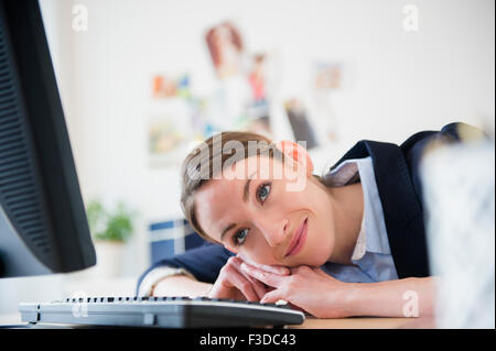 Woman leaning on her desk in office - Stock Photo