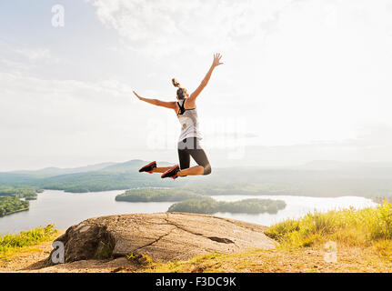 Young woman jumping over mountain top, rear view - Stock Photo