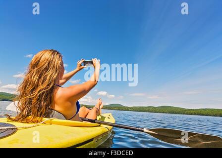 Young woman taking selfie in kayak on lake