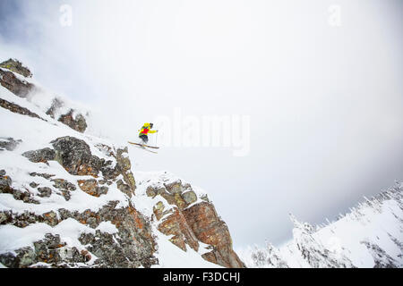 Skier jumping off rocky mountain - Stock Photo