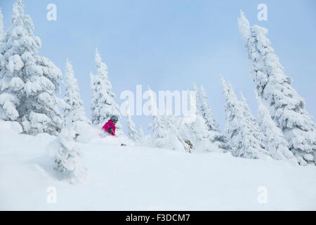 Low angle view of mature woman on ski slope - Stock Photo