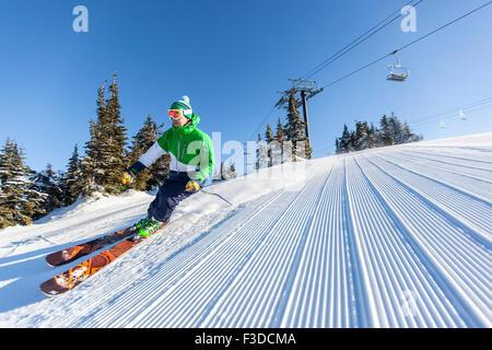 Mature man on ski slope under blue sky - Stock Photo