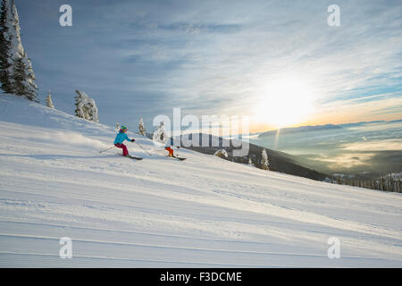 Couple skiing at sunset - Stock Photo
