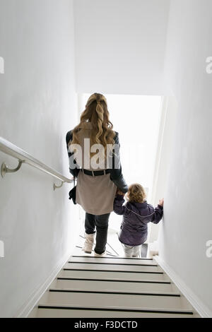 Mother and son (4-5) walking down stairs - Stock Photo