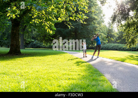 Mother and son (12-13) exercising in park - Stock Photo