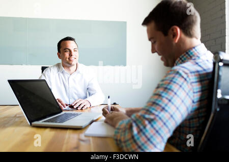 Man being interviewed in conference room - Stock Photo