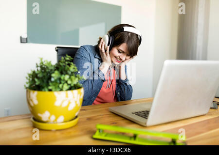 Young woman listening to music in office - Stock Photo
