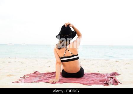 Woman in bikini relaxing on beach - Stock Photo