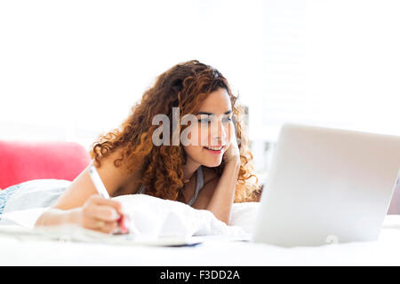 Woman with laptop in bed - Stock Photo