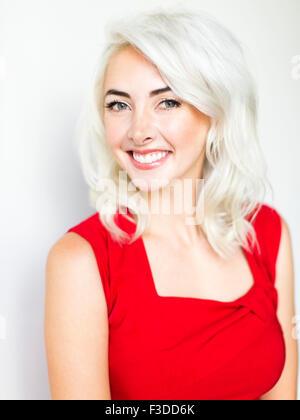 Studio shot of woman wearing red dress - Stock Photo
