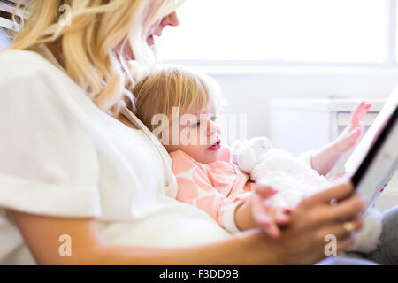 Mother reading book with daughter (2-3) - Stock Photo
