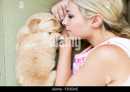 Portrait of puppy with owner lying down on sofa - Stock Photo