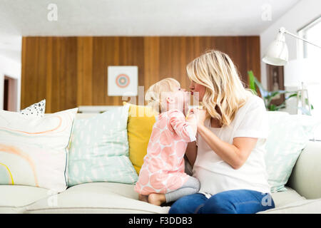 Woman kissing daughter (2-3) in living room - Stock Photo
