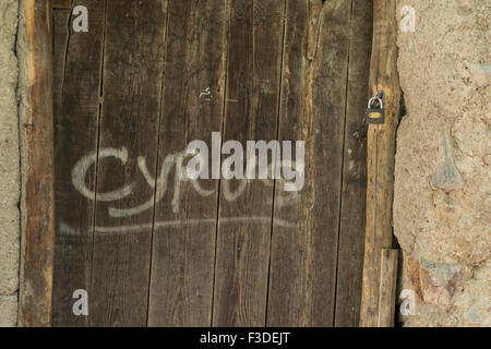 Old padlock hanging on a weathered wooden door with a text on the door planks. - Stock Photo