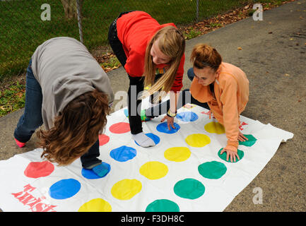 Teen and pre-teen girls playing Twister floor game. - Stock Photo