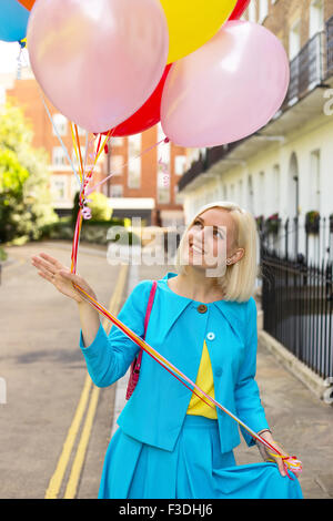 young woman holding balloons - Stock Photo