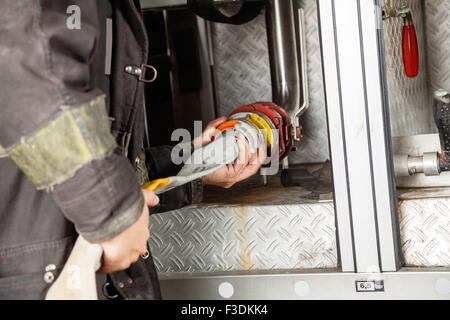 Firewoman Adjusting Hose In Firetruck - Stock Photo