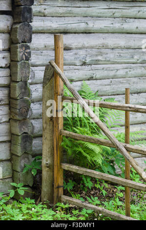 Log cabin wall and wooden gate - Stock Photo