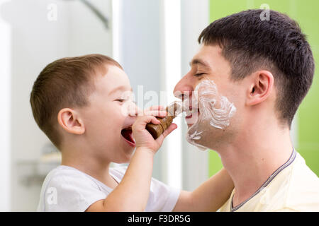 Cute child boy shaving his father in bathroom - Stock Photo